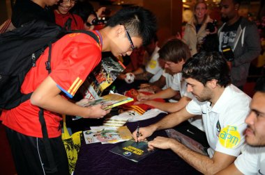 Spanish soccer star Raul Gonzalez Blanco of New York Cosmos, second right, signs an autograph for a fan at a signing event in Hong Kong, China, 16 February 2015.