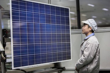 A Chinese worker checks a solar panel at a photovoltaic (PV) power plant in Ganyu county, Lianyungang city, east China's Jiangsu province, 24 February 2015.