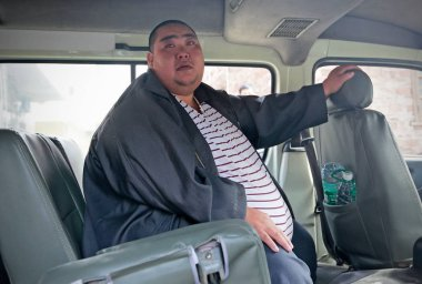 China's fattest man Deng Guiliang sits in a minibus as he is going to a hospital for weight loss surgery in Guangzhou city, south China's Guangdong province, 15 December 2015