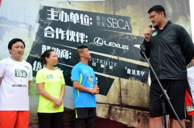 Retired Chinese basketball superstar Yao Ming, right, speaks during the ceremony to start the challenge of running 100 marathons in 100 consecutive days in Guangzhou city, south China's Guangdong province, 2 April 2015