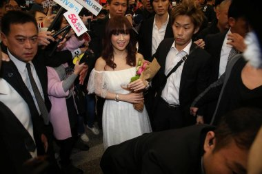 Japanese singer Ayumi Hamasaki, center, is surrounded by reporters at the Taipei Songshan Airport after arriving in Taipei, Taiwan, 14 February 2015.