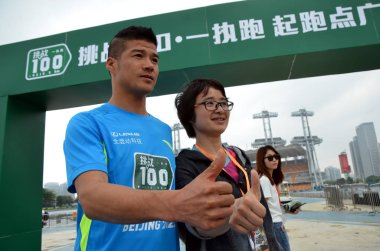 China's first international ultra-marathon champion Chen Penbin, left, poses with a fan during the ceremony to start the challenge of running 100 marathons in 100 consecutive days in Guangzhou city, south China's Guangdong province, 2 April 2015