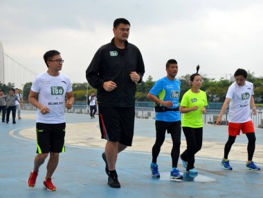 China's first international ultra-marathon champion Chen Penbin, in blue, retired Chinese basketball superstar Yao Ming, tallest, and Chinese tennis player Zheng Jie, in green, run during the ceremony to start the challenge of running 100 marathons i