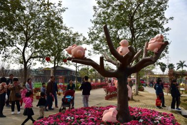 People visit pig sculptures displayed on the tree branches to mark the upcoming Spring Festival or Chinese Lunar New Year (Year of Pig) at a scenic spot in Foshan city, south China's Guangdong province, 27 January 2019