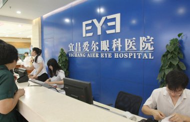 Chinese employees work at the reception desk of Yichang Aier Eye Hospital in Yichang city, central Chinas Hubei province, 28 June 2012.