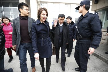 Kim Lee, third left, the ex-wife of Crazy English founder Li Yang, walks out of Chaoyang District Peoples Court in Beijing, China, 13 February 2014