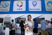--FILE--A model poses at the stand of Tencent during the 2014 Global Mobile Internet Conference (GMIC 2014) in Beijing, China, 5 May 2014