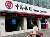 A pedestrian walks past a branch of Bank of China (BOC) in Yichang city, central Chinas Hubei province, 23 September 2013