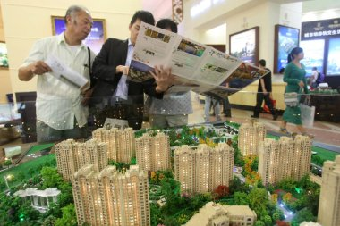 Chinese homebuyers look at an introduction in front of models of residential apartment buildings during a real estate fair in Shanghai, China, 6 October 2013