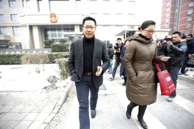 Li Yang, left, founder of Crazy English, walks out of Chaoyang District Peoples Court in Beijing, China, 13 February 2014