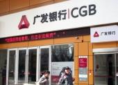 Local citizens walk past a branch of China Guangfa Bank (CGB) in Nanjing, east Chinas Jiangsu province, 21 March 2013.