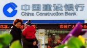 Pedestrians walk past a branch of CCB (China Construction Bank ) in Shanghai, China, 16 February 2013