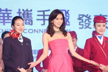 Taiwanese model and actress Lin Chi-ling, center, performs with air hostesses of China Eastern Airlines, left, and China Southern Airlines, right, during a signing ceremony by four major Taiwanese and Chinese Mainland airlines teaming up to strengthe