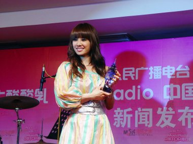 Taiwanese singer Jolin Tsai poses holding her trophy for Annual Top singer during the awards ceremony by Music Radio, the only pop station under China National Radio, in Beijing, China, 27 January 2013.