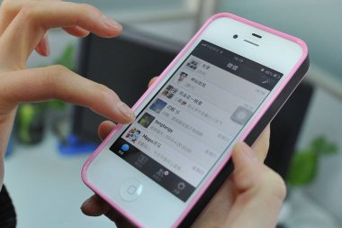 A Chinese woman uses mobile messaging app Weixin, or WeChat, of Tencent on her Apple iPhone 4S smartphone in Dalian city, northeast Chinas Liaoning province, 23 April 2013