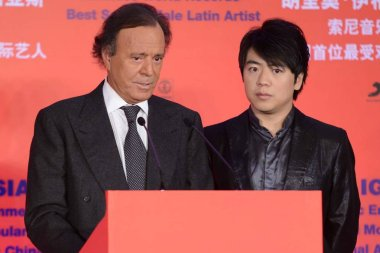 Spanish singer-songwriter Julio Iglesias, left, speaks next to Chinese pianist Lang Lang after being presented with a Guinness World Record for Best Selling Male Latin Artist in the World at a press conference in Beijing, China, 1 April 2013