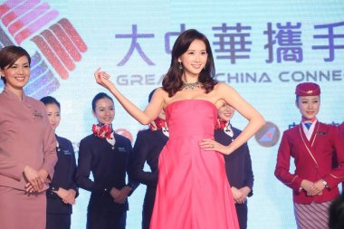 Taiwanese model and actress Lin Chi-ling, center, poses with air hostesses during a signing ceremony by four major Taiwanese and Chinese Mainland airlines teaming up to strengthen their services on lucrative routes carrying passengers between Taiwan