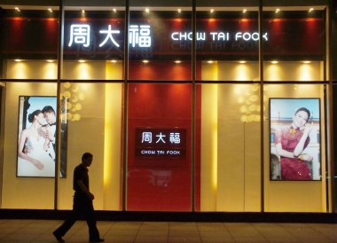 A pedestrian walks past a jewelry shop of Chow Tai Fook in Yichang city, central Chinas Hubei province, 3 September 2013.
