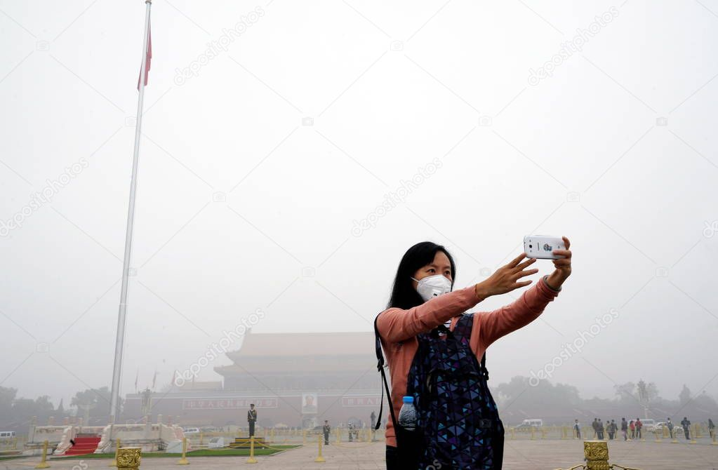 A tourist wearing a face mask takes selfies on the Tian'anmen Square in heavy smog in Beijing, China, 11 October 2014