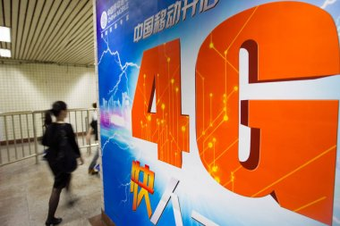 A pedestrian walks past an advertisement for China Mobile 4G networks at a metro station in Shanghai, China, 25 May 2013