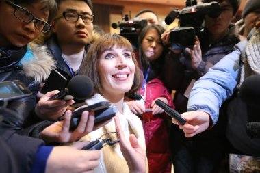 Kim Lee, center, wife of Crazy English founder Li Yang, is interviewed after a trial at the Beijing Chaoyang District Peoples Court in Beijing, China, 3 February 2013