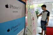 A customer is seen next to an advertisement for new iPhone 5s and iPhone 5c smartphones of Apple at a branch of China Unicom in Shanghai, China, 17 September 2013