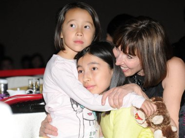 Kim Lee, right, wife of Crazy English founder Li Yang, and their daughters attend an activity by UN Women in Beijing, China, 30 January 2013