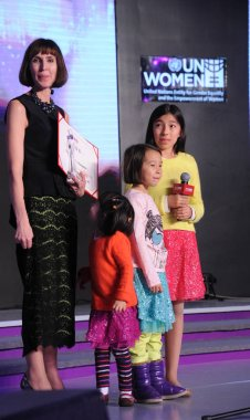 Kim Lee, left, wife of Crazy English founder Li Yang, and their daughters attend an activity by UN Women in Beijing, China, 30 January 2013