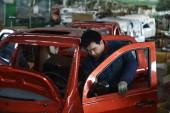 Egy kínai munkás összeállítja az autót a futóművet egy Autógyár Zouping megyében, East chinas Shandong tartomány, 16 december 2014.