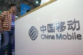 A Chinese employee is seen next to the stand of China Mobile at the 15th China International Industry Fair 2013 in Shanghai, China, 7 November 2013
