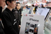 A customer looks at a brochure of iPhone smartphone of Apple at a branch of China Unicom in Hangzhou city, east Chinas Zhejiang province, 13 January 2012
