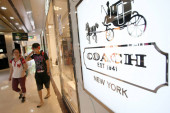 Pedestrians walk past a boutique of Coach at a shopping mall in Shanghai, China, 3 July 2014.