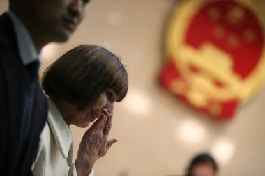 Kim Lee, right, wife of Crazy English founder Li Yang, weeps during the trial at the Beijing Chaoyang District Peoples Court in Beijing, China, 3 February 2013
