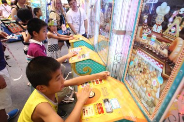 Young kids play electronic video games during the 9th China International Cartoon and Games Expo, known as CCG Expo 2013, in Shanghai, China, 11 July 2013