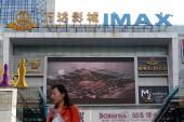 A pedestrian walks past a Wanda Cinema IMAX in Shanghai, China, 1 December 2014