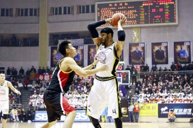--FILE--Kenyon Martin of Xinjiang Guanghui Flying Tigers Basketball Club, right, challenges a player of Jilin Northeast Tigers Basketball Club in a 13th round match of the 2011-2012 CBA regular season in Urumqi city, northwest Chinas Xinjiang Uygur A