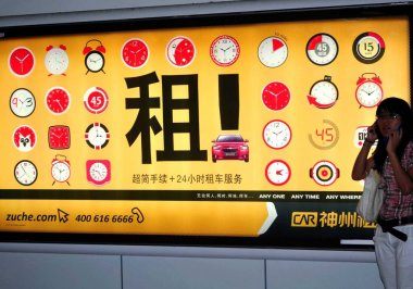 A passenger talks on her mobile phone next to an advertisement for China Auto Rental (CAR) in Shanghai, China, 3 September 2011