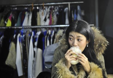 Chinese model Xiao Ya eats buns during a break of a photography session for an online garment shop at a studio in Chengdu ctiy, southwest China's Sichuan province, 19 October 2014