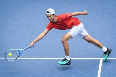 Taro Daniel of Japan returns a shot to Zhang Ze of China in their group match of the men's singles during the 2019 Davis Cup by BNP Paribas Qualifier in Guangzhou city, south China's Guangdong province, 1 February 2019.