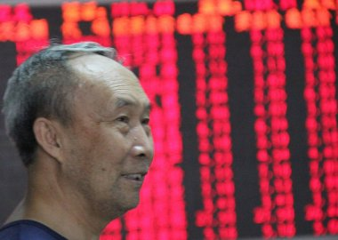 A Chinese investor smiles as he looks at prices of shares (red for price rising and green for price falling) at a stock brokerage house in Qingdao, east Chinas Shandong province, 1 August 2013