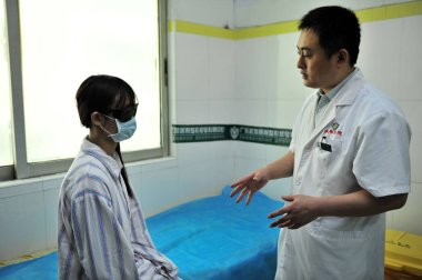 --FILE--19-year-old young woman, Xiao hui, talks with a doctor about her breast augmentation surgery at a hospital in Guangzhou city, south Chinas Guangdong province, 8 November 2012.