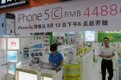 Chinese salesmen welcome customers at a store of iPhone 5c in Haikou, south Chinas Hainan province, 26 September 2013