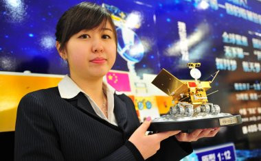 A Chinese clerk shows a scale model of Chinas first moon rover The Jade Rabbit at a store in Shenyang city, northeast Chinas Liaoning province, 15 December 2013