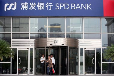 People walk out from a branch of SPD Bank (Shanghai Pudong Development Bank) in the Lujiazui Financial District in Pudong, Shanghai, China, 22 June 2011