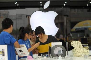 A Chinese staff member introduces the iPhone 4S smartphone to customers in an Apple authorized store in Nantong city, east Chinas Jiangsu province, 13 October 2012