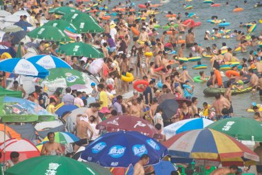 Holidaymakers crowd the Fujiazhuang Beach Resort on a scorching day in Dalian city, northeast Chinas Liaoning province, 28 July 2012.