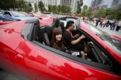 Egy fiatal pár ül a Ferrari sportkocsi sorakoznak fel másokkal során a felvonulás, hogy megünnepeljék a 20 éves a Ferraris jelenléte Kínában, a Guangzhou város, Dél-chinas Guangdong tartomány, 22 november 2012
