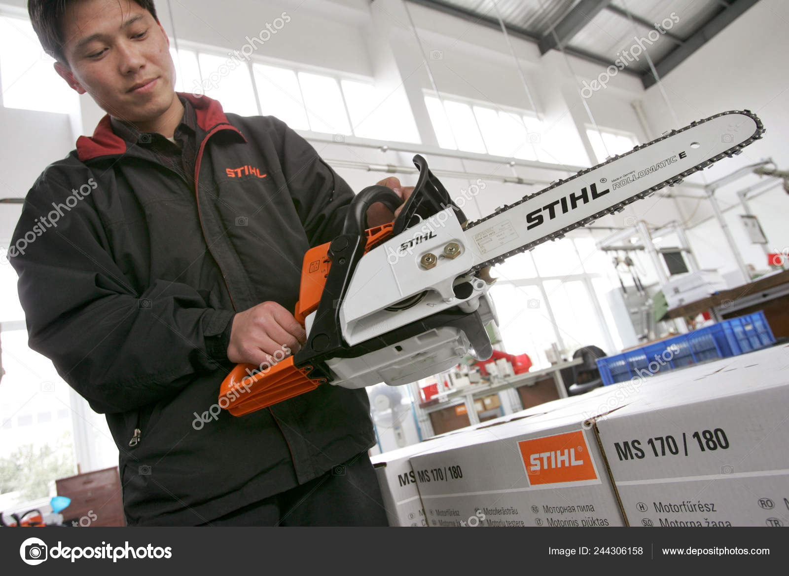 Chinese Worker Shows Electric Motor Saw Warehouse Plant