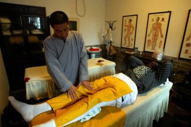 NBA star Mickael Pietrus is treated by a therapist from Shaolin Temple in Zhengzhou, central Chinas Henan province, 7 November 2011.