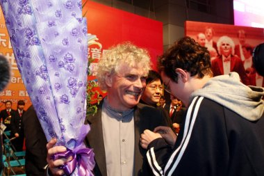 A local high school student pins a school badge to the lapel of Sir Simon Rattle, left, principal conductor of the Berlin Philharmonic, after the live broadcast of the concert of the Berlin Philharmonic on the Nanjing Road shopping street in Shanghai